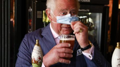 Prince Charles takes a sneaky sip of beer while visiting local businesses